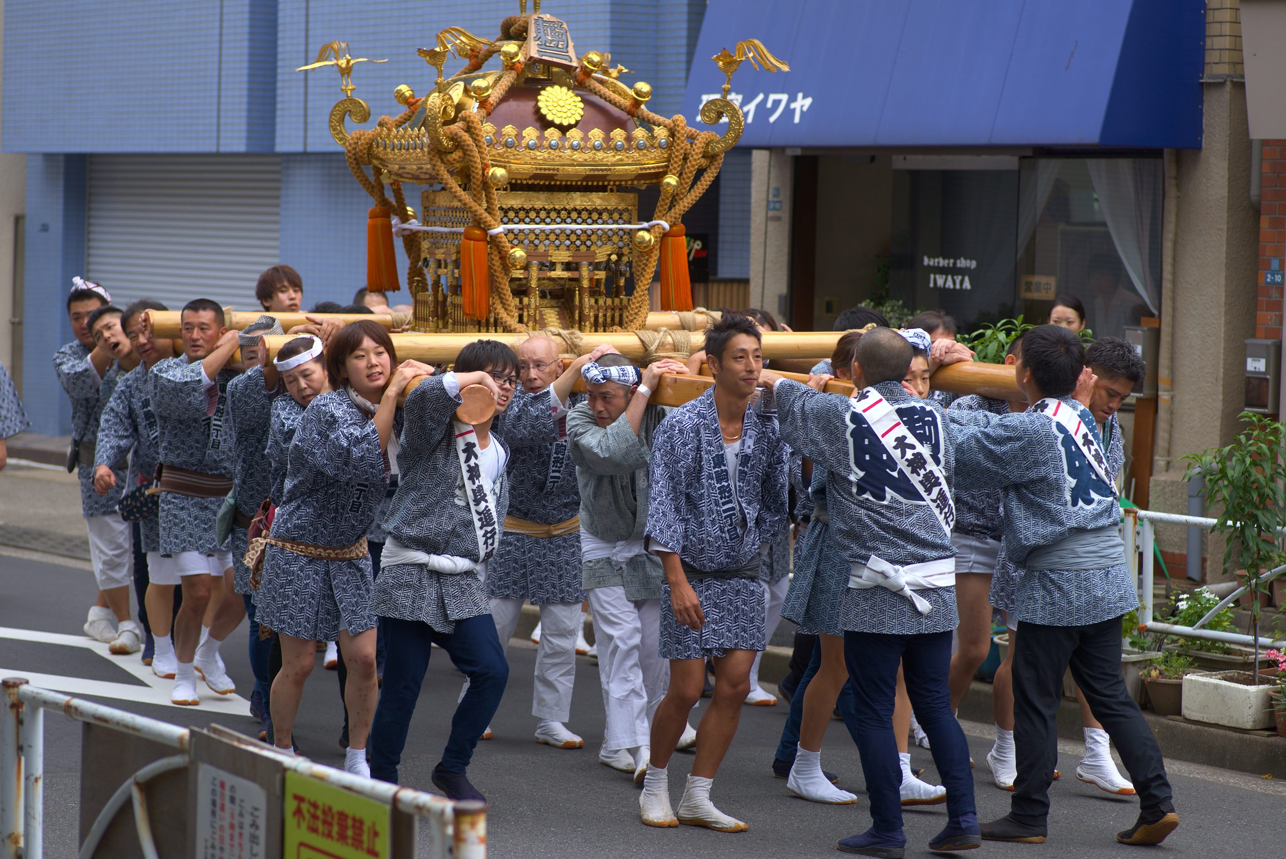 25 young people corrying a mikoshi and chanting