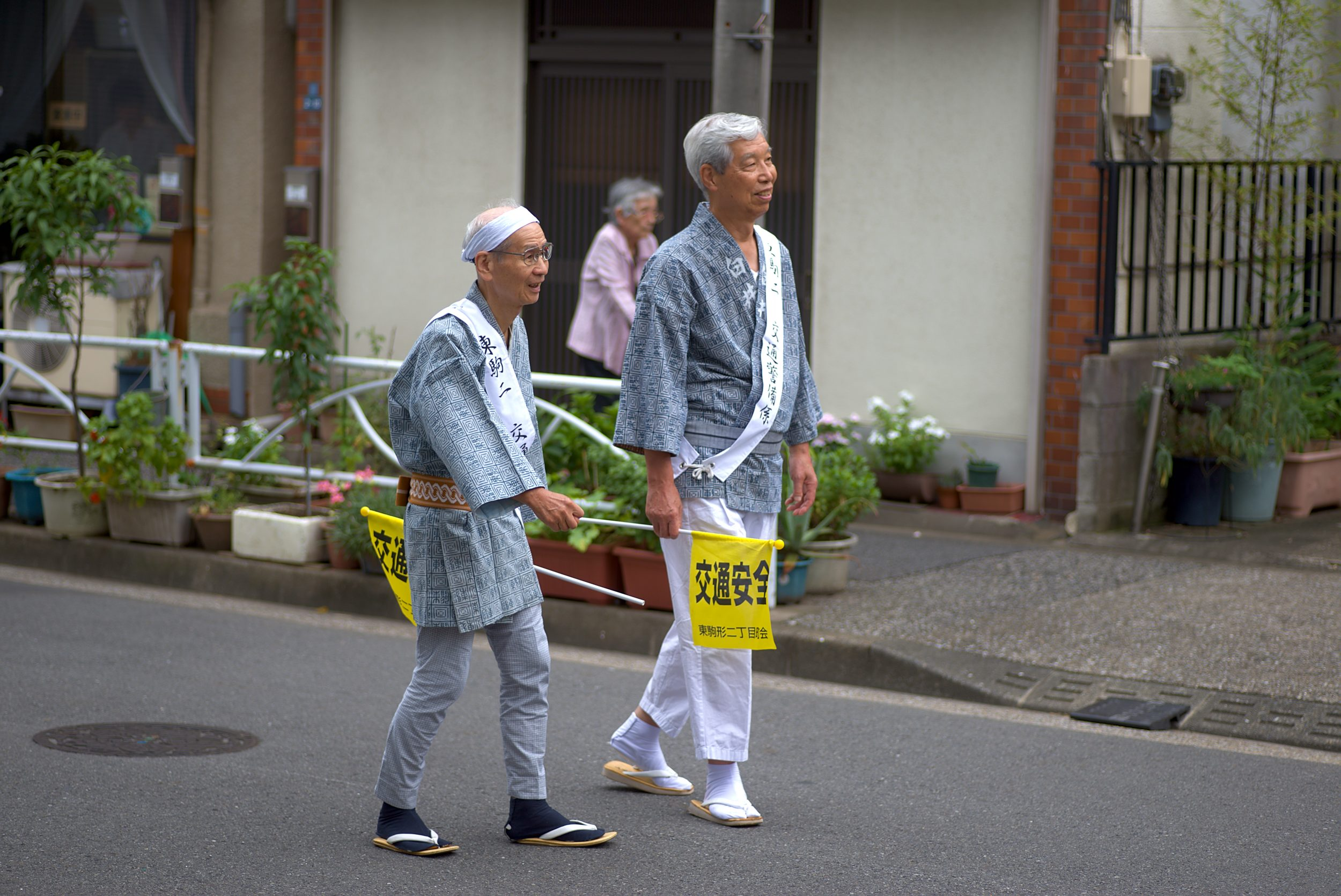 Two old man walking on the street with small yellow flags