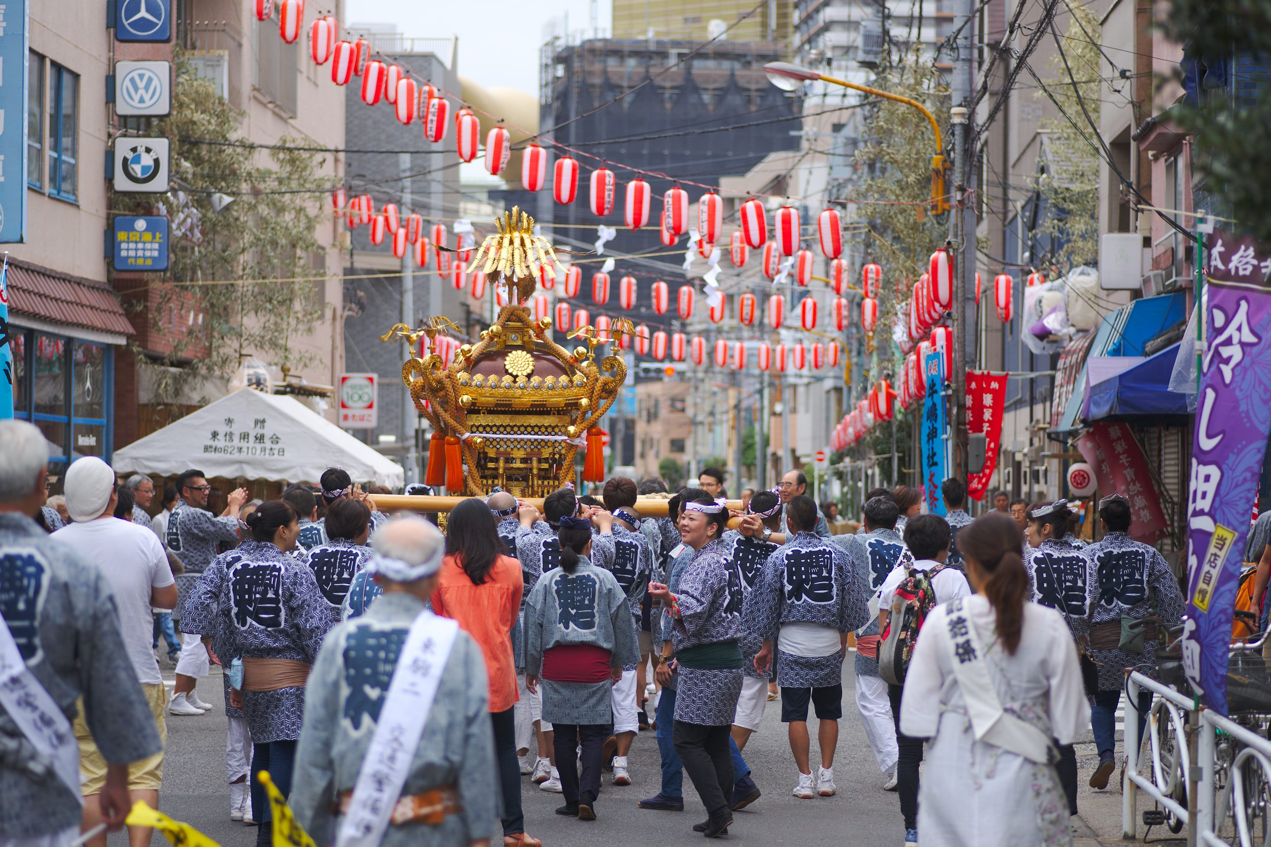 People carrying a mikoshi, red lamps hanging over them